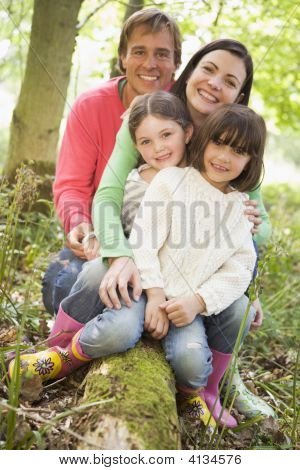 Families Outdoors In Woods Sitting On Log Smiling