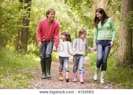Familias caminando por el sendero cogidos de la mano sonriendo