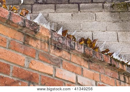 Broken Glass Bottles On Top Of Brick Wall