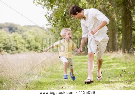 Father And Son Running On Path Holding Hands Smiling