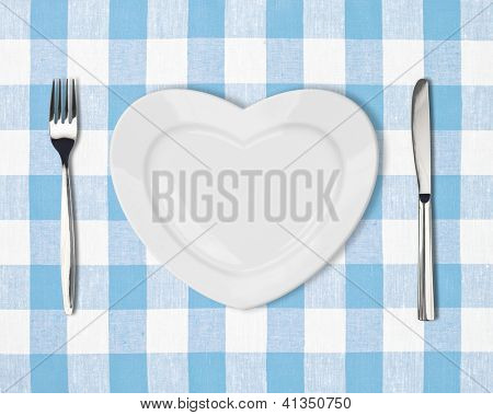 Knife, white plate and fork on blue checked tablecloth