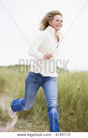Woman Running At Beach Smiling