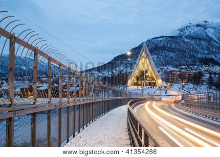 TROMSO, NORWAY - DECEMBER 30: Arctic Cathedral shines at dusk on December 30, 2012. This Church is  the most famous landmark in Tromso Norway, the church was designed by the architect Jan Inge Hovig.