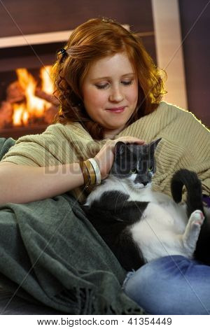 Teenage girl sitting at fireplace at home and fondling cat, affectionate smiling.