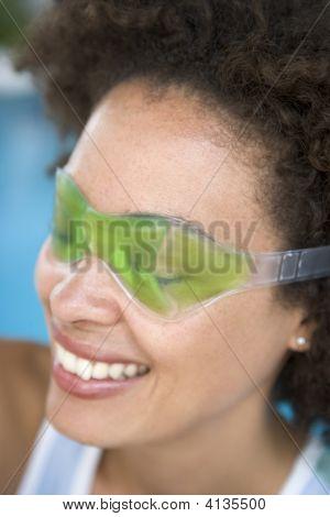 Woman Sitting Poolside Using Eye Mask Smiling