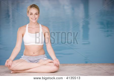 Woman Sitting Poolside Doing Yoga Smiling