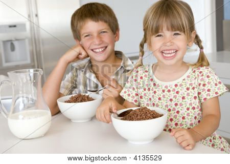 Two Young Children In Kitchen Eating Cereal Smiling