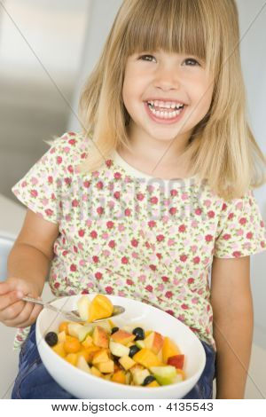 Young Girl In Kitchen Eating Bowl Of Fruit Smiling