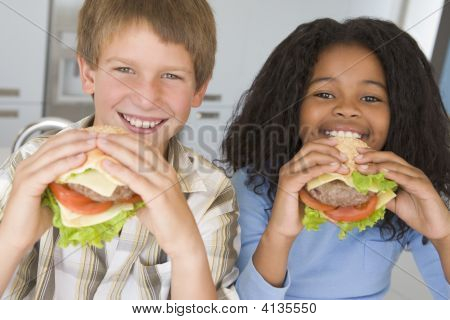 Two Young Children In Kitchen Eating Cheeseburgers Smiling