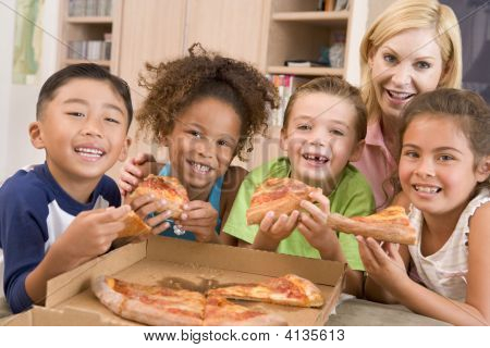 vier junge Kinder Innenaufnahme mit Woman eating Pizza lächelnd