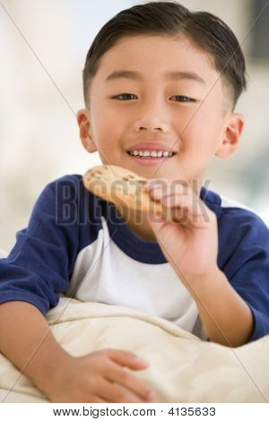 Young Boy Eating Cookie In Living Room Smiling