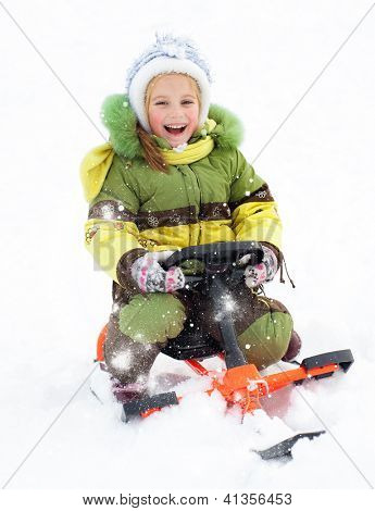 Happy litte girl with children's snowmobile