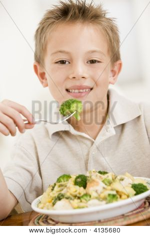 Young Boy Indoors Eating Pasta With Brocolli Smiling