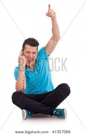 hombre joven hablando por teléfono y vitoreando, sobre un fondo blanco sentado