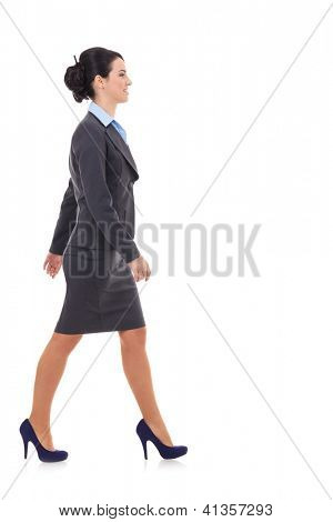 Side view of a business woman walking isolated over a white background