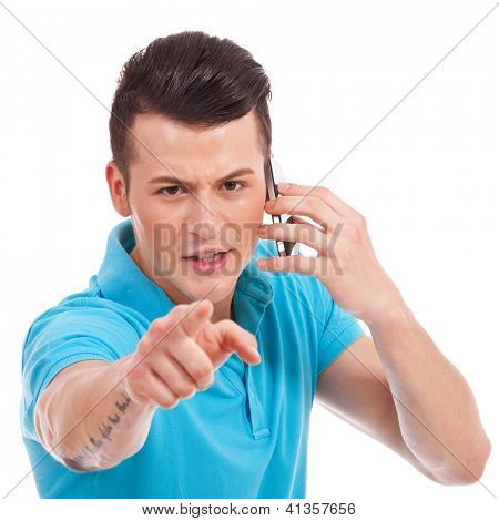waist-up picture of an attractive young casual man pointing and looking angrily at the camera while speaking on the phone