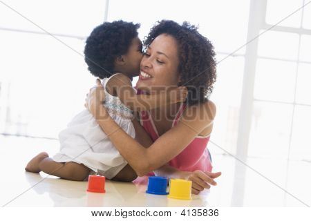 Mother And Daughter Indoors Kissing And Smiling