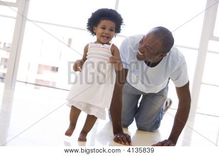 Father And Daughter Indoors Playing And Smiling