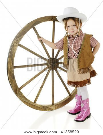 An adorable preschool cowgirl looking mad as she stands propping up a large wooden wagon wheel.  On a white background.