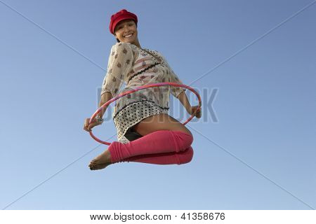 Motion blur shot of a full length portrait of a woman jumping with hula hoop against blue sky