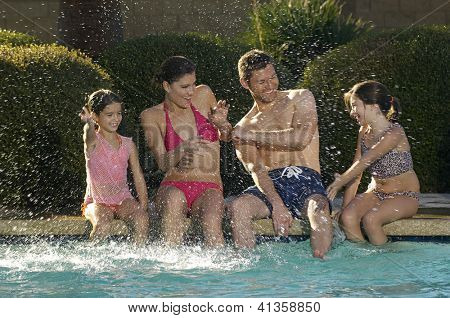 Happy family enjoying together while sitting at the edge of the swimming pool