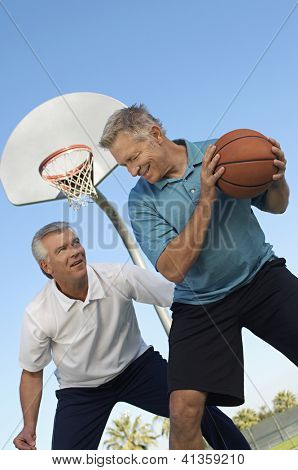 Low angle view of two men playing basketball at court