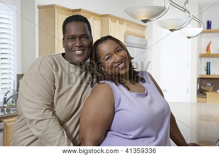 Portrait of an obese African American couple standing together in kitchen