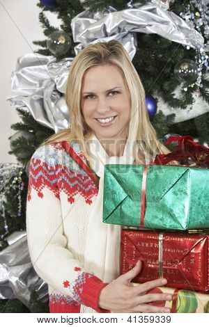 Portrait of a happy Caucasian female standing with gift boxes and Christmas tree in the background