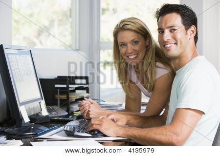 Couples In Home Office With Computer Smiling