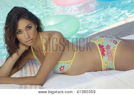 Portrait of a beautiful woman resting on lounge chair at resort with swimming pool in the background