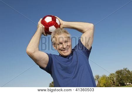 Low angle view portrait of a happy middle aged man throwing football against blue sky