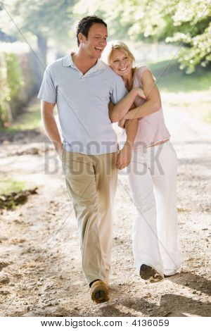 Couples Walking Outdoors Arm In Arm Smiling