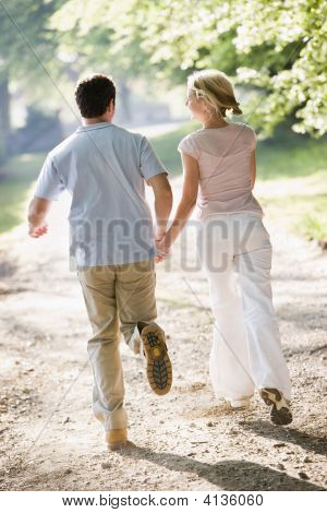 Couples Running Outdoors Holding Hands