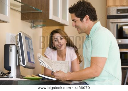 Couples In Kitchen With Computer And Newspaper Smiling
