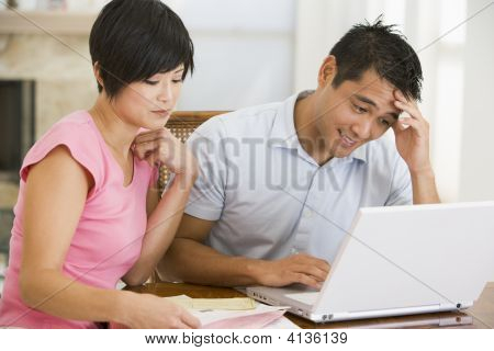 Couples In Dining Room With Laptop Looking Unhappy
