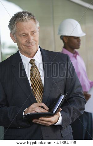 Happy middle aged businessman holding dairy with male architect in the background