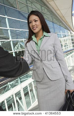 Beautiful Asian businesswoman greeting male colleague in front of office