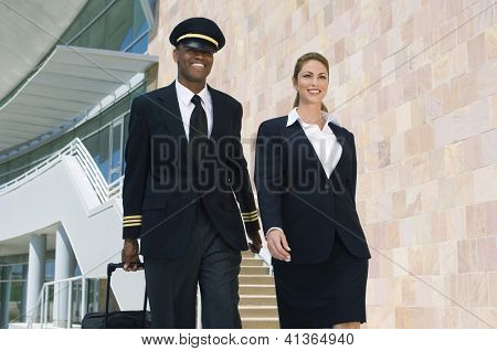 Airplane cabin crew walking together at the airport with bags