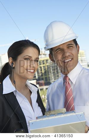 Male architect with female colleague looking away outdoors