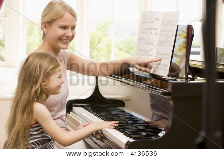 Woman And Young Girl Playing Piano And Smiling