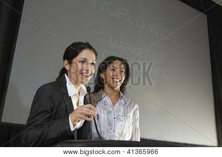 Happy businesswomen giving a lecture at podium