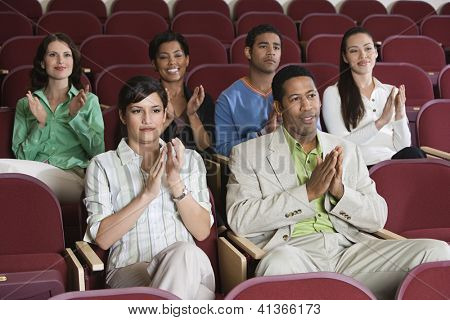 Group of multiethnic people applauding at a performance while sitting in auditorium