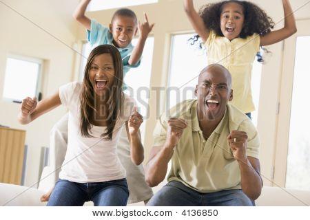 Familien im Wohnzimmer Jubel und lächelnd