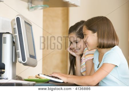 Two Young Girls In Kitchen With Computer Smiling