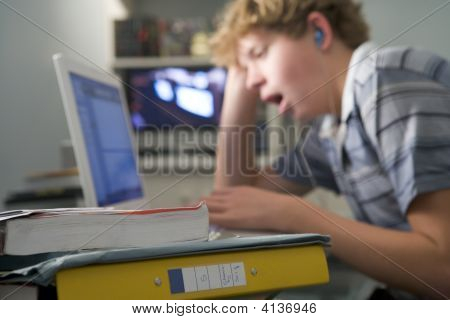 Young Boy In Bedroom Yawning Using Laptop And Listening To Mp3 Player