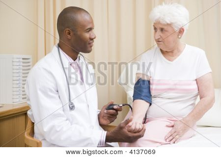 Doctor Checking Woman'S Blood Pressure In Exam Room
