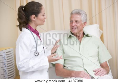 Doctor Giving Checkup To Man In Exam Room Smiling