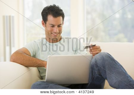 Man In Living Room Using Laptop And Holding Credit Card Smiling