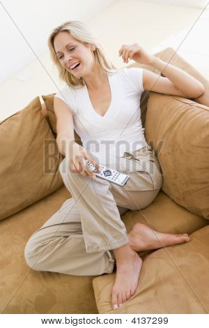 Woman In Living Room Holding Remote Control Smiling
