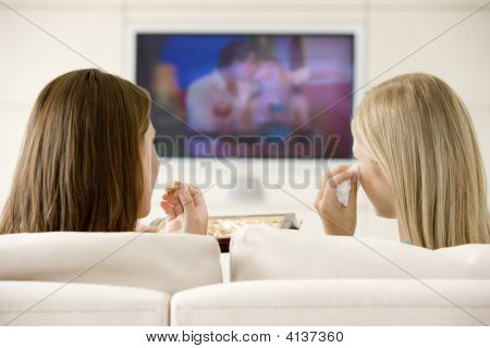 Two Women In Living Room Watching Television Eating Chocolates And Crying